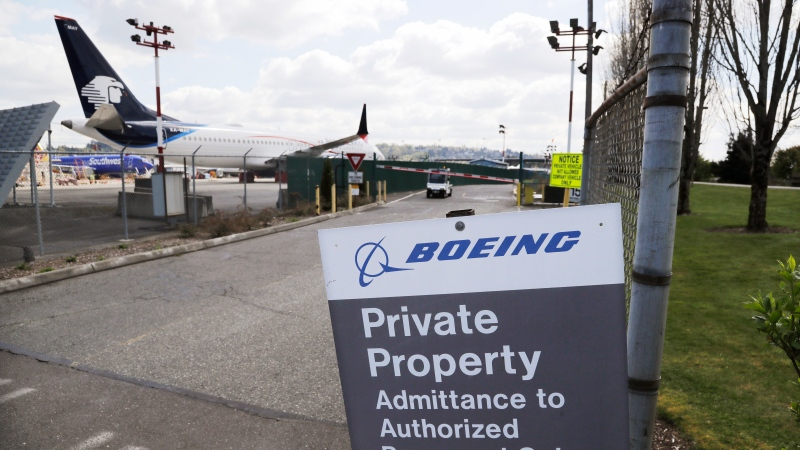 In this April 20, 2020, file photo, planes sit parked behind a sign marking Boeing property at a Boeing production plant in Renton, Wash. (AP Photo/Elaine Thompson)