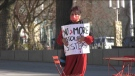 """A woman holds a sign that says """"No more stolen sisters"""" on Red Dress Day in Edmonton. May 5, 2021. (CTV News Edmonton)"""