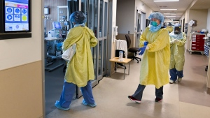 ICU health-care workers enter a negative pressure room to care for a COVID-19 patient on a ventilator at the Humber River Hospital during the COVID-19 pandemic in Toronto on Wednesday, December 9, 2020. THE CANADIAN PRESS/Nathan Denette