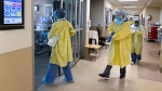 ICU health-care workers enter a negative pressure room to care for a COVID-19 patient on a ventilator in Toronto on Wednesday, December 9, 2020. THE CANADIAN PRESS/Nathan Denette