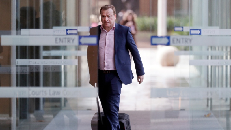 Andrew Cooper, founder and president of libertarian group LibertyWorks, arrives at Federal Court in Sydney, Thursday, May 6, 2021. (AP Photo/Rick Rycroft)