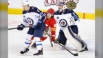 Calgary Flames' Andrew Mangiapane, centre, battles between Winnipeg Jets goalie Connor Hellebuyck and Neal Pionk during first period NHL hockey action in Calgary on Wednesday, May 5, 2021. THE CANADIAN PRESS/Larry MacDougal