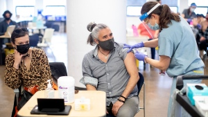 Jules Mccusker receives a BioNTech Pfizer COVID-19 vaccine from Dr. Shauna Martiniuk, right, an emergency doctor with  Mount Sinai Hospital, as Jowite Bydlowska, left, sits alongside him at a pop-up vaccination clinic run by the Waakebiness-Bryce Institute for Indigenous Health and the University of Toronto Dalla Lana School of Health, in Toronto, Saturday, April 10, 2021. The vaccination centre serves Toronto's Indigenous community. THE CANADIAN PRESS/Chris Young