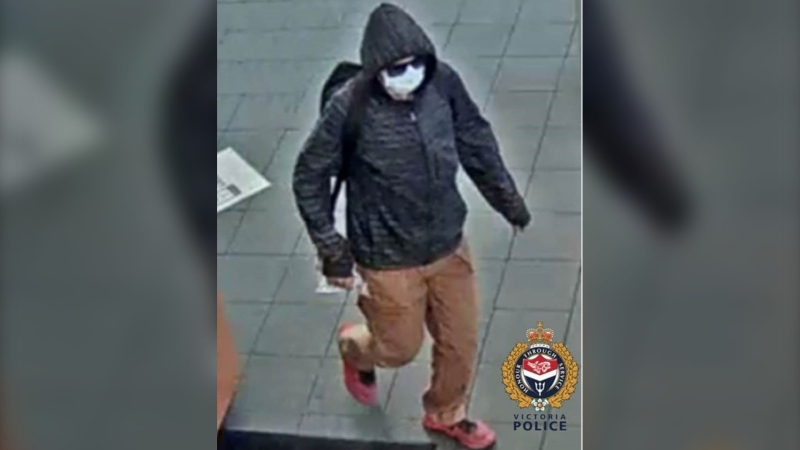 The perpetrator is described as a white man, standing five feet, six inches tall. He was wearing a black hoodie, brown pants, red shoes, black-rimmed sunglasses and a blue medical mask. (VicPD)