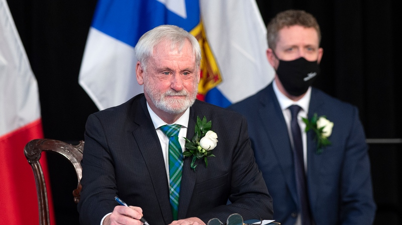 Nova Scotia Premier Iain Rankin, right, looks on as Keith Irving signs his oath of office in Halifax on Tuesday, Feb. 23, 2021. Rankin has named Irving as environment minister. THE CANADIAN PRESS/Andrew Vaughan
