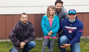 Chris Prest, left, Ren Rivers and Alec Daviau pose with Emilia Fontana, the seven-year-old girl they rescued from drowning in the Blanche River on May 2. (Lydia Chubak/CTV News)