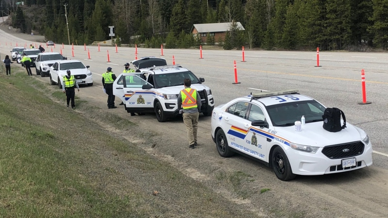 RCMP officers prepare to begin stopping vehicles to enforce B.C.'s COVID-19 travel restriction near Manning Park on May 6, 2021.