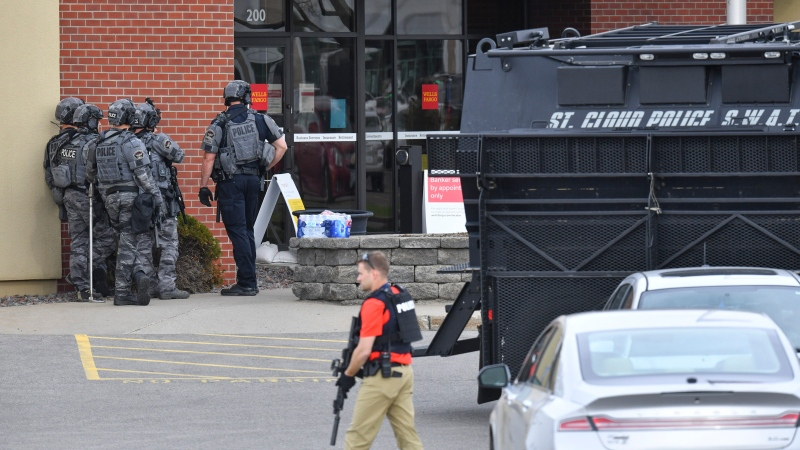Officers stand near an entrance to the Wells Fargo branch Thursday May 6, 2021, in south St. Cloud, Minn. following a reported hostage situation. Police in Minnesota were on the scene Thursday of a reported bank robbery with hostages. (Dave Schwarz/St. Cloud Times via AP)