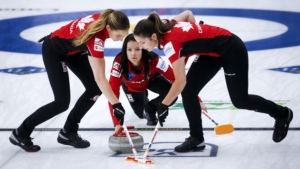 Team Canada skip Kerri Einarson, centre, makes a shot as lead Briane Meilleur, left, and second Shannon Birchard sweep against Denmark at the Women's World Curling Championship in Calgary, Alta., Thursday, May 6, 2021. Canada defeated Denmark 10-8 Thursday morning, but lost to Japan in the afternoon draw 7-5. (THE CANADIAN PRESS/Jeff McIntosh)