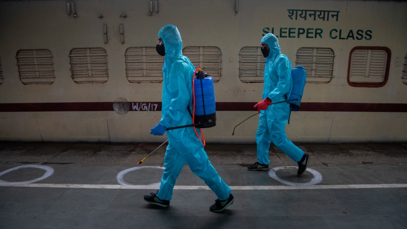 Health workers in personal protective equipment sanitize a train prepared as COVID-19 care centre in the wake of spike in the number of positive coronavirus cases, at a railway station in Gauhati, India, Thursday, May 6, 2021. (AP Photo/Anupam Nath)