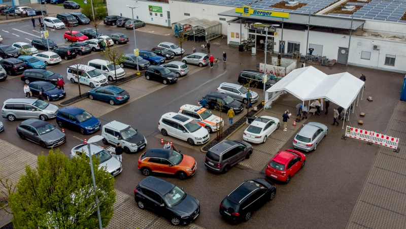 In this file photo dated Wednesday, May 5, 2021, cars with people waiting for AstraZeneca vaccination queue in front of a tent on the parking lot of a supermarket in Pforzheim, southern Germany. (AP Photo/Michael Probst, FILE)