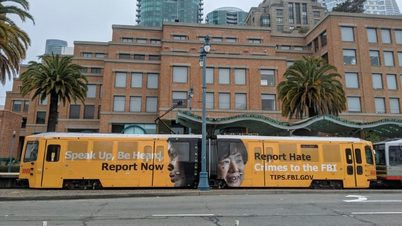 An ad on a San Francisco city train reads 'Speak Up, Be Heard, Report Now. Report Hate Crimes to the FBI.' (FBI via AP)