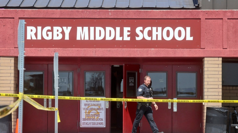 A police officer walks out of Rigby Middle School following a shooting there earlier Thursday, May 6, 2021, in Rigby, Idaho. Authorities said that two students and a custodian were injured, and a female student has been taken into custody. (AP Photo/Natalie Behring)