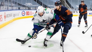 Edmonton Oilers' Alex Chiasson (39) and Vancouver Canucks' Jayce Hawryluk (13) battle for the puck during first period NHL action in Edmonton on Thursday, May 6, 2021.THE CANADIAN PRESS/Jason Franson