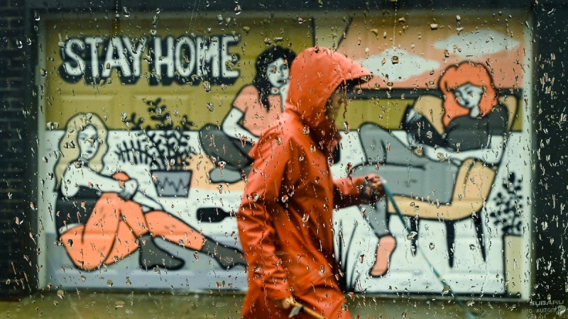 A person walks past a COVID-19 mural designed by artist Emily May Rose on a rainy day during the COVID-19 pandemic in Toronto on April 12, 2021. (Nathan Denette /  THE CANADIAN PRESS)