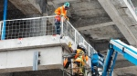 Construction workers work at a downtown site Tuesday, February 9, 2021 in Montreal, Quebec. THE CANADIAN PRESS/Ryan Remiorz