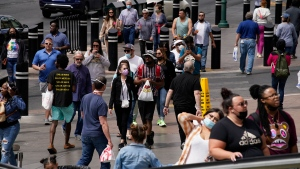 Masked and unmasked pedestrians walk along the Las Vegas Strip, Tuesday, April 27, 2021, in Las Vegas. (AP Photo/John Locher)