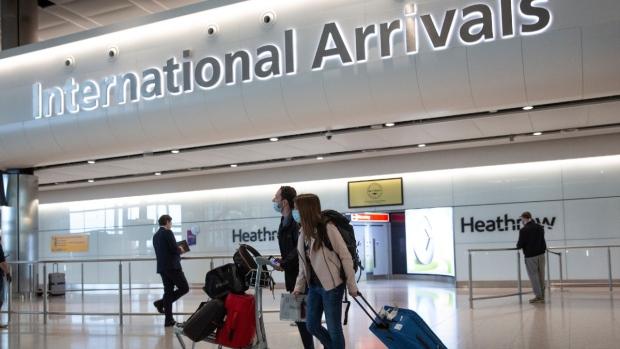 Passengers wearing face masks arrive at London's Heathrow Airport, on June 8, 2020. (Matt Dunham / AP)