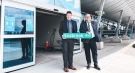 Michael Seabrook, left, who is retiring as CEO of the London International Airport, holds a new road sign with his name. (Source: London International Airport)