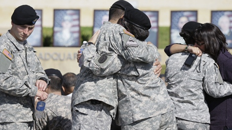 Soldiers comfort each other before the start of memorial service for the Fort Hood shooting victims, Tuesday, Nov. 10, 2009 at Fort Hood, Texas. (AP / Donna McWilliam)