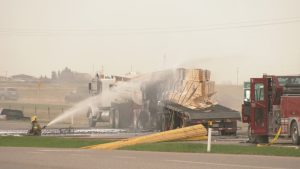 Fire crews douse a load of lumber following Friday morning's fatal crash on Hwy. 3 near Kipp.