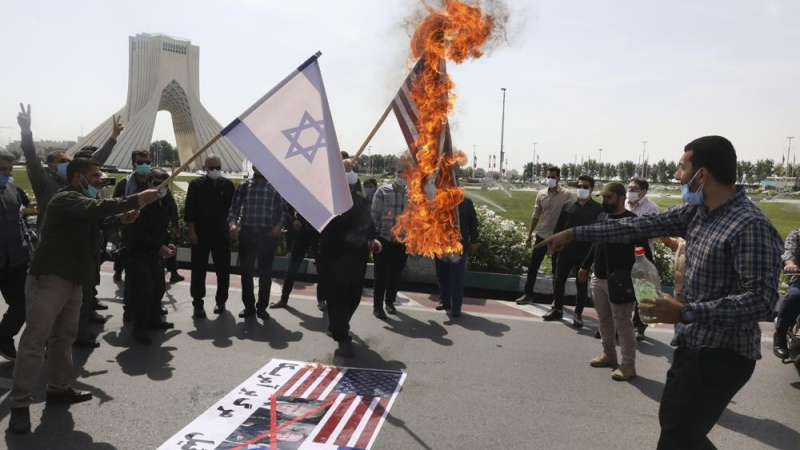 Demonstrators burn representations of Israeli and U.S flags during the annual Al-Quds, or Jerusalem, Day rally, with the Azadi (Freedom) monument tower seen at left, in Tehran, Iran, Friday, May 7, 2021. (AP Photo/Vahid Salemi)
