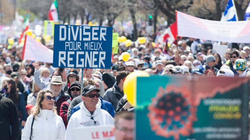 People take part in a demonstration outside the Olympic Stadium opposing the Quebec government's measures to help curb the spread of COVID-19 in Montreal, Saturday, May 1, 2021. Two busloads of protesters may have been exposed to COVID-19, health authorities say. THE CANADIAN PRESS/Graham Hughes