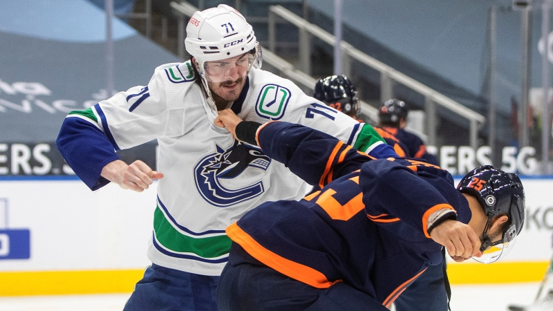 Edmonton Oilers' Darnell Nurse (25) and Vancouver Canucks' Zack MacEwen (71) fight during third period NHL action in Edmonton on Thursday, May 6, 2021.THE CANADIAN PRESS/Jason Franso