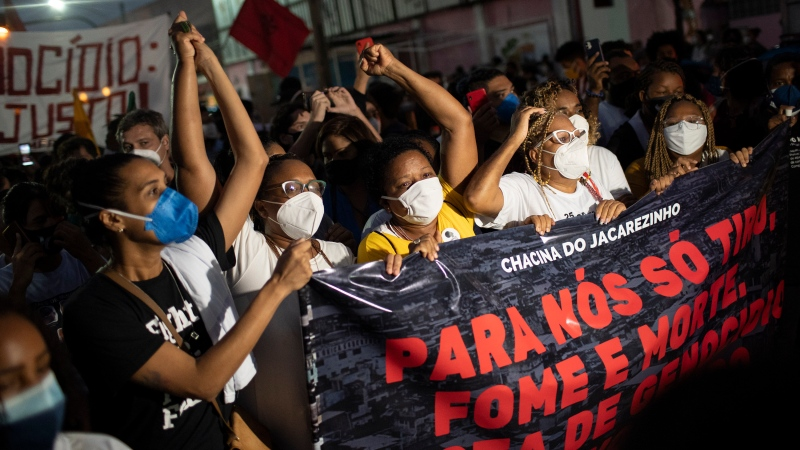 "Residents hold a banner with a message that reads in Portuguese; ""For us, only shootings, hunger and death. No more genocide"", during a protest a day after a deadly police operation in the Jacarezinho favela of Rio de Janeiro, Brazil, Friday, May 7, 2021. (AP Photo/Silvia Izquierdo)"