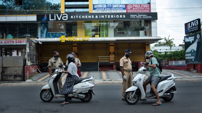 Policemen check the credentials of commuters during a lockdown imposed to curb the spread of coronavirus in Kochi, Kerala state, India, Saturday, May 8, 2021. (AP Photo/R S Iyer)