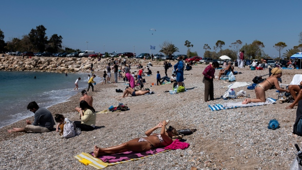 People enjoy a sunny day at a beach of Glyfada suburb west of Athens, Saturday, April 3, 2021. Greece has relaxed some coronavirus restrictions despite surging COVID-19 cases that are straining hospitals to their limits, with retail stores to reopen and people allowed to drive outside their home municipalities for exercise on weekends. (AP Photo/Yorgos Karahalis)