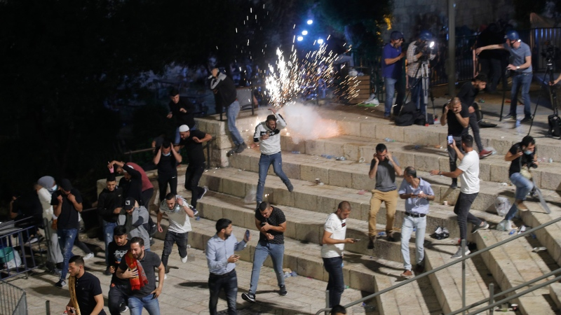 Palestinians run from stun grenades fired by Israeli police officers during clashes at Damascus Gate just outside Jerusalem's Old City, Saturday, May 8, 2021. (AP Photo/Oded Balilty)