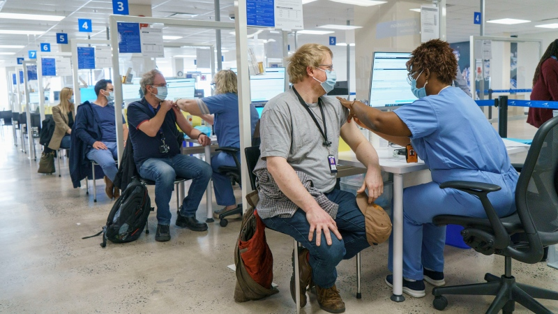 Employees are vaccinated at a COVID-19 vaccination clinic at CAE headquarters in Montreal, on Monday, April 26, 2021. THE CANADIAN PRESS/Paul Chiasson