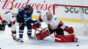 Ottawa Senators goaltender Filip Gustafsson (32) saves the shot by Winnipeg Jets' Blake Wheeler (26) as Artem Zub (2) defends during second period NHL action in Winnipeg on Saturday, May 8, 2021. (THE CANADIAN PRESS/John Woods)