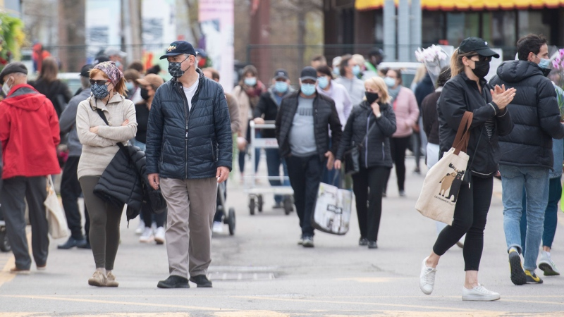 People wear face masks as they shop at the Atwater Market in Montreal, Saturday, May 8, 2021, as the COVID-19 pandemic continues in Canada and around the world. THE CANADIAN PRESS/Graham Hughes