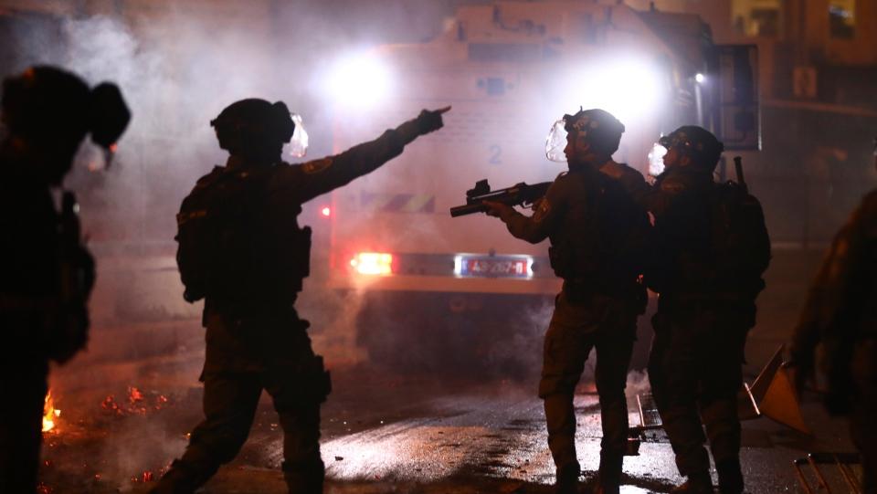 Israeli police officers fire stun grenades