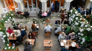 People sit at tables in the open area of Covent Garden Market, in London, Thursday, April 15, 2021. (AP Photo/Alberto Pezzali)