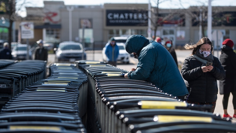 A person fills out paperwork on the shopping carts as they line up to receive a COVID-19 vaccine at a Loblaws grocery store pharmacy in Ottawa, on Monday, April 26, 2021. THE CANADIAN PRESS/Justin Tang