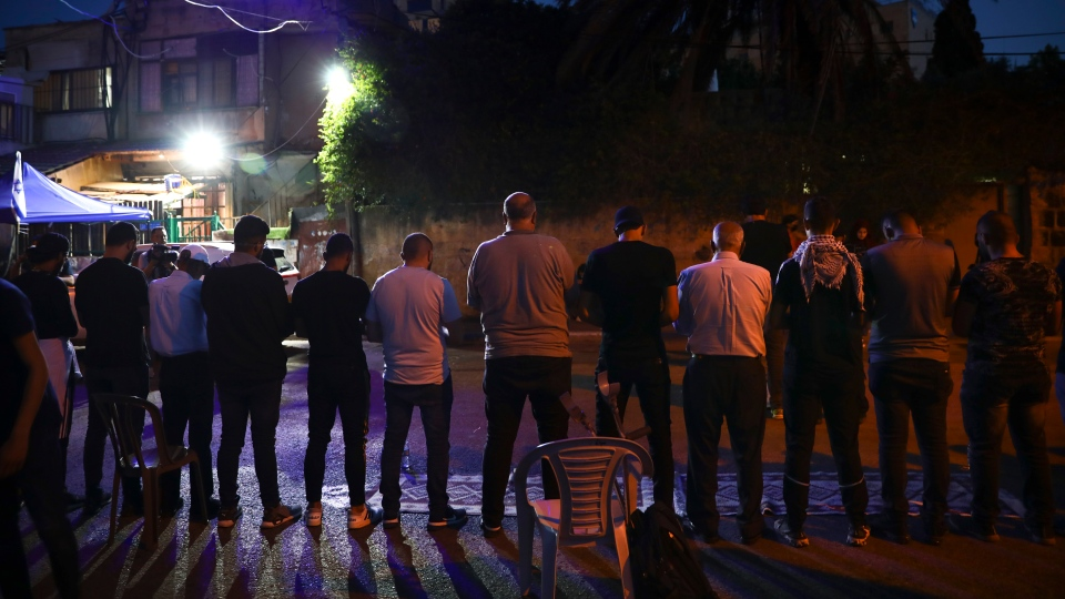 Palestinians pray after Iftar meal