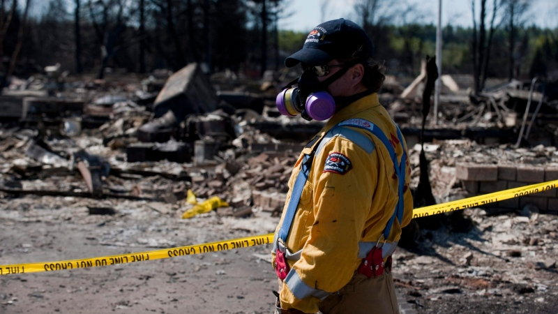 Crews work to shut off gas and water in a burned-out neighbourhood in Slave Lake, Alta., on Wednesday, May 18, 2011. Almost all of Slave Lakes's 7,000 residents fled Sunday in the face of a forest fire that eventually destroyed about a third of the town (The Canadian Press/Ian Jackson)