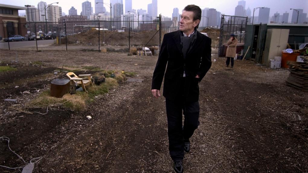 Architect Helmut Jahn walks through a vacant lot