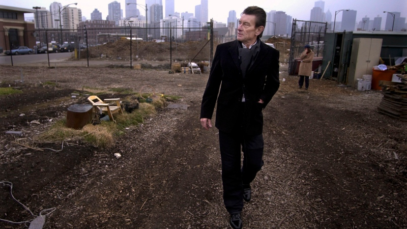 In this March 4, 2004 file photo, architect Helmut Jahn walks through a vacant lot on Chicago's near north side. Jahn, a prominent German architect who designed an Illinois state government building and worked on the design of the FBI headquarters in Washington, was killed when two vehicles struck the bicycle he was riding outside Chicago. Jahn, 81, was struck Saturday, May 8, 2021, afternoon while riding north on a village street in Campton Hills, about 55 miles (90 kilometers) west of Chicago. (AP Photo/M. Spencer Green File)