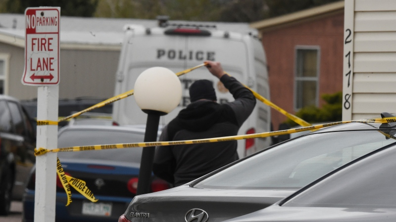A Colorado Springs Police Department officer lifts up crime tape at the scene where multiple people were shot and killed early Sunday, May 9, 2021, in Colorado Springs, Colo. (Jerilee Bennett/The Gazette via AP)