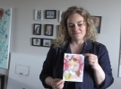 "Maria Kelebeev shows off her watercolour ""Seeing Red"", focused on infant loss and infertility at her Innisfil, Ont. home on Sun. May 9, 2021 (Siobhan Morris/CTV News)"