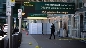An RCMP officer works at the scene after a shooting outside the international departures terminal at Vancouver International Airport, in Richmond, B.C., Sunday, May 9, 2021. THE CANADIAN PRESS/Darryl Dyck