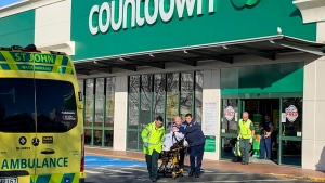First responders take a victim to an ambulance outside a Countdown supermarket in central Dunedin, New Zealand, Monday May 10, 2021. (NZME via AP)