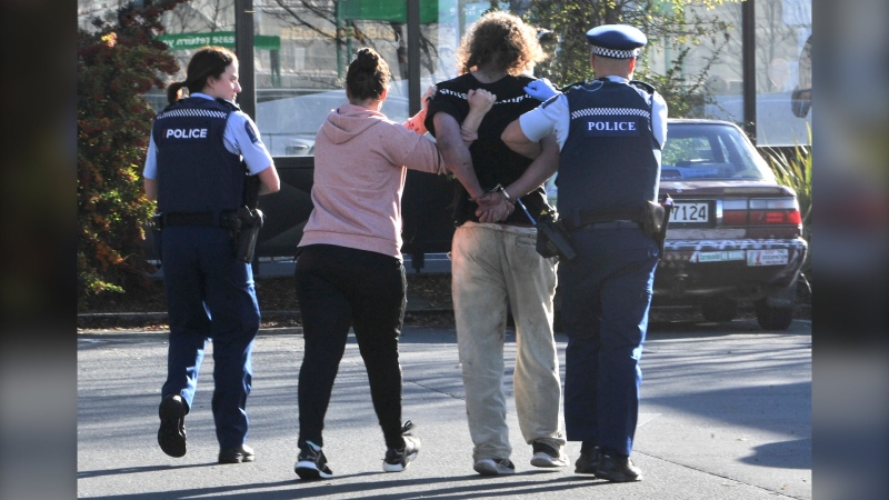 Police take a suspect into custody near the Countdown supermarket in central Dunedin, New Zealand, on May 10, 2021. (Otago Daily Times via AP)