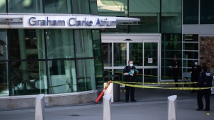 An RCMP officer speaks with colleagues as a broken window is seen after a one person was killed during a shooting outside the international departures terminal at Vancouver International Airport, in Richmond, B.C., Sunday, May 9, 2021. THE CANADIAN PRESS/Darryl Dyck