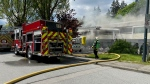 A fire broke out at a mixed residential and commercial building in Surrey on 138th Street near the Fraser Highway on Monday, May 10, 2021. (CTV News Vancouver/Jordan Jiang)