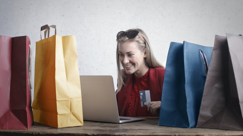 A woman uses a laptop while surrounded by shopping bags in this file photo. (Andrea Piacquadio / Pexels)